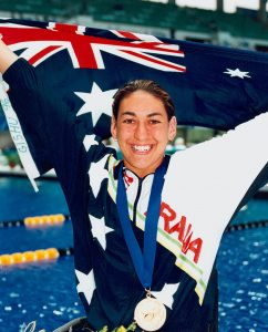 Australian S8 swimmer Priya Cooper on the pool deck with the Australian flag, gold medal and flowers after a medal presentation ceremony at the 1996 Atlanta Paralympic Games