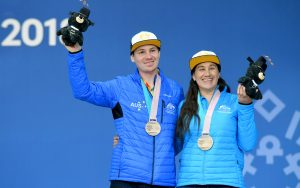 An image of Melissa Perrine and Christian Geiger wearing their medals and smiling