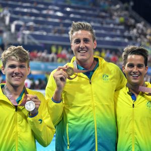 Image of 3 Australian Para-swimmers dressed in gold tracksuits, smiling at the camera and holding medals in their left handss.