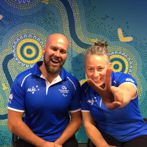 An image of Ryley Batt and Danni Di Toro in official merchandise of Paralympics Australia. Both of them are smiling and Danni is flashing a victory sign for the camera.