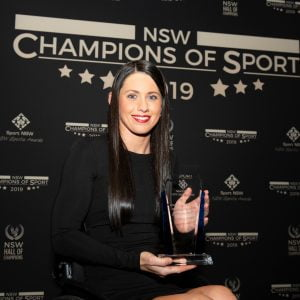 An image of a parathlete holding a trophy at the NSW Champions of Sport awards ceremony