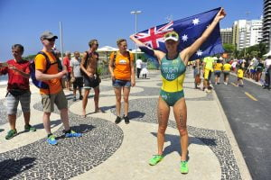An image of Kate Doughty smiling and holding up the Australian flag