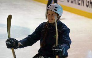 Image of a female athlete playing para-ice hockey