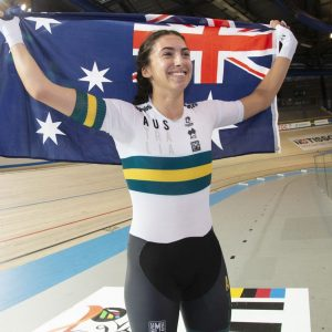 An image of para-cyclist Paige Greco smiling and holding the Australia flag