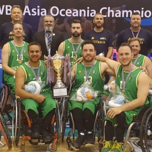 An image of a para-athlete team with the winners cup and medals