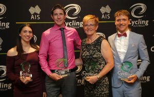 An image of four para-cyclists in an award ceremony, holding their awards and smiling