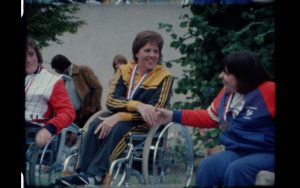 female paralympian smiling shaking hands with competitor