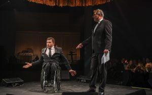 Kurt doing a speech in a suit in a wheelchair