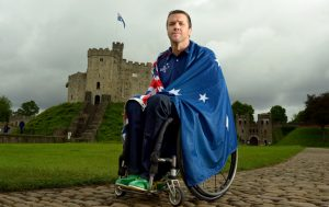 Male Paralympian Greg Smith in a wheelchair draped in the Australian flag