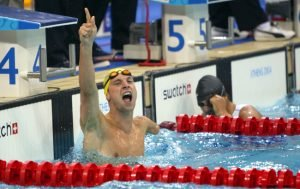 Male paralympic swimmer celebrates winning a race