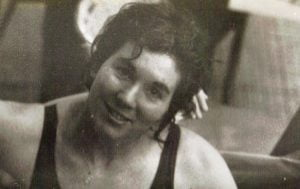 Female Paralympic swimmer smiling at the camera