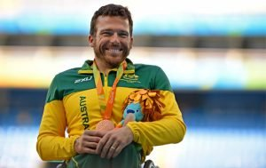 Male Paralympian Kurt Fearnley dressed in green and gold tracksuit representing Australia at the Rio 2016 Paralympic Games. Shown with a medal around his neck and a toy in his arms. He is smiling at the camera.