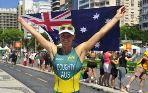 Australian Paralympian Kate Doughty standing with her arms outstretched above her head holding the Australian flag