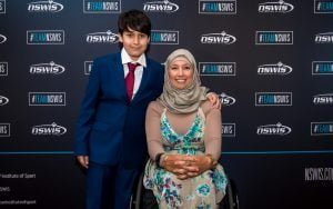 Image of female in a wheelchair - Para archer Ameera Lee - and her son, Huthaifa, standing next to her