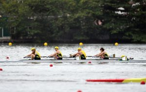 Image of 4 rowers in a boat on the water