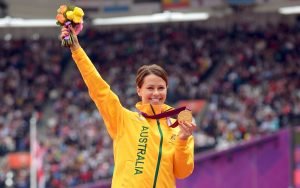 Kelly Cartwright standing on the medal podium holding a gold medal