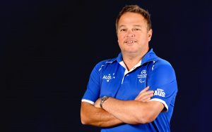 Profile photo of Australian Wheelchair Basketball coach Craig Friday in a blue polo, with his arms folded across his chest, smiling at the camera