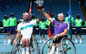 Australian wheelchair tennis players Heath Davidson and Dylan Alcott holding a trophy above their heads and smiling