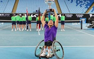 Australian wheelchair tennis player Dylan Alcott smiling at the camera and lifting a trophy above his head