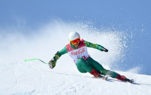 Image of male skier wearing a green ski suit with a white and red competitor bib.