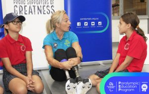 Image of Australian Paralympian Eliza Ault-Connell sitting with 2 female school students talking.