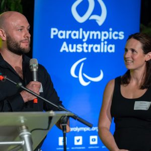 Image of male standing holding a microphone in his right hand speaking and a female standing to his left. They are both standing in front of a blue backdrop with the Paralympics Australia logo