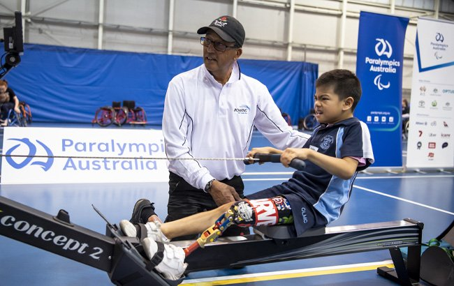Image of a young male left leg amputee on a rowing machine being supervised by an adult