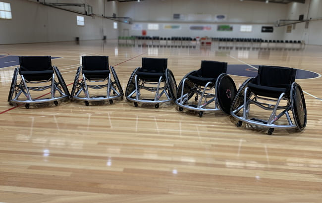 5 empty wheelchairs in a row on an indoor basketball court