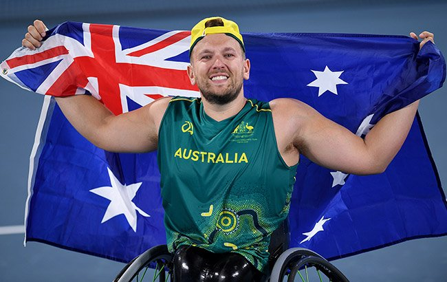 Australian wheelchair tennis player Dylan Alcott reacts to winning gold at Tokyo 2020 Paralympic Games. He is holding an Australian flag behind him