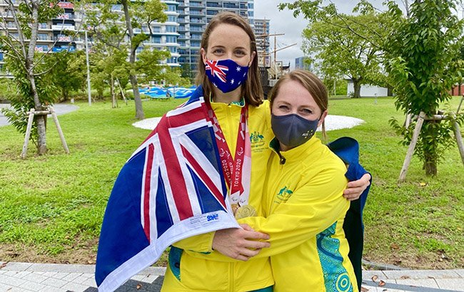 Australian Paralympian Ellie Cole and Australian Paralympic Team chef de mission Kate McLoughlin are wearing their Australian team tracksuits, face masks, and are hugging.