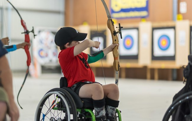 Boy in wheelchair and red t-shirt aiming archery bow at targets to the right